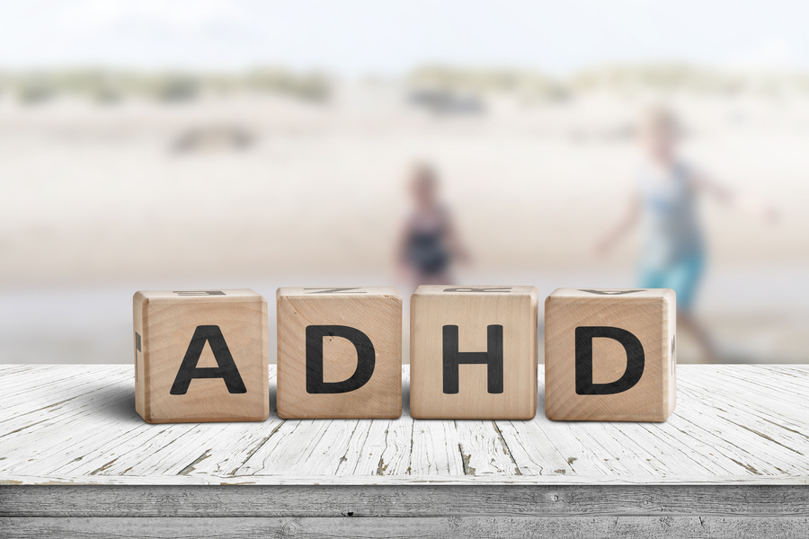 ADHD sign on a wooden table with kids acting wild in the background