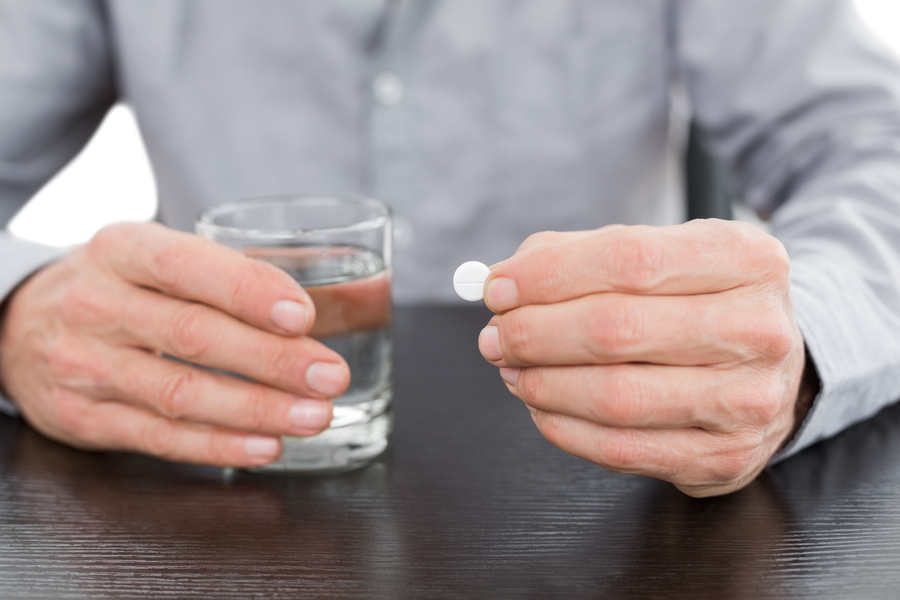 mid-section-of-a-man-holding-glass-of-water-and-pill